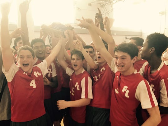Players on Fair Lawn's boys volleyball team hold up the North 1 trophy after their team's win over Lakeland.