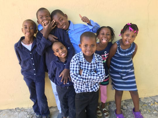 Chika, right, and her friends from the Have Faith Haiti Orphanage in December 2015. She was excited to see them after returning from Michigan. In Haiti, she was back in her bunk in a crowded room of 13 other girls.