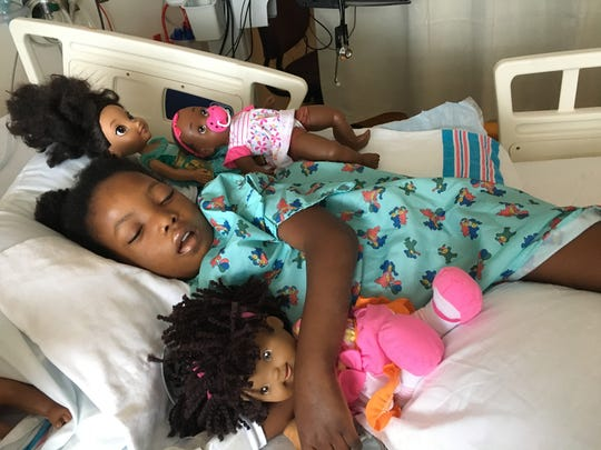 After a blood infection in July 2016, Chika, 6, lays in bed surrounded by her dolls at Mott Children's Hospital in Ann Arbor. The infection was traced back to an intravenous port that was inserted. It was then removed.