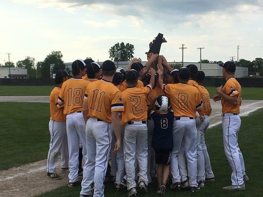 The Algonac baseball team celebrates its district championship at Marine City High School.