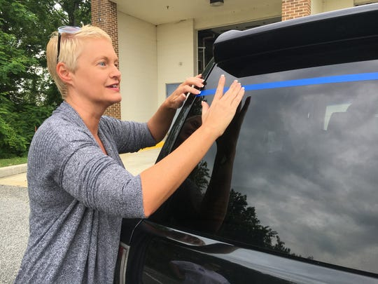 """Jennifer Cohan, secretary of the Delaware Department of Transportation, affixes a strip of blue tape to a vehicle during Saturday's """"Back the Blue"""" fundraiser for the Delaware State Troopers Association."""