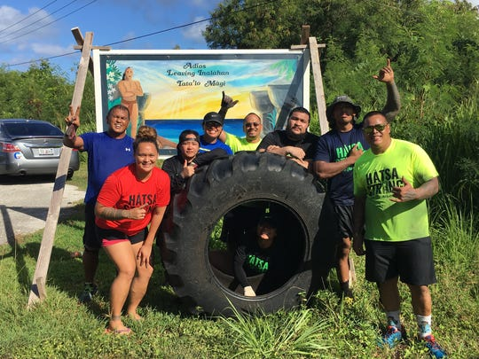 Celebrity trainer Ray Chargualaf, second from right, with his team of supporters who helped him flip a giant tire for more than eight hours in order to complete a personal fitness challenge.