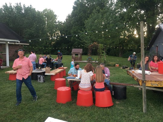Salvaged pecan wood planks set on top of buckets made for creative outdoor seating at this yard party.