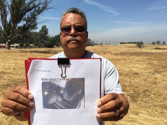 Angel Valentin, a former Coachella Valley Unified transportation official, holds a printed screenshot from video footage the district has said does not exist.