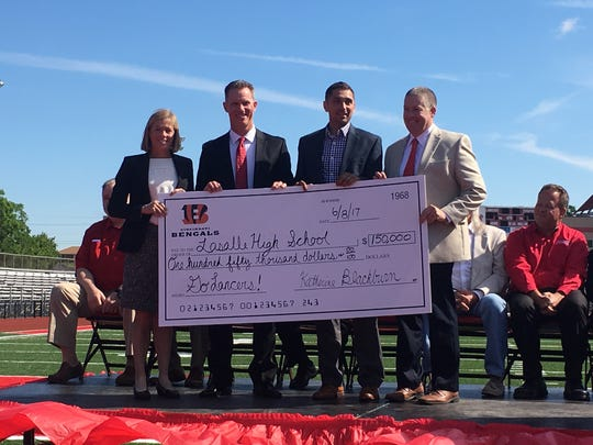 Representatives from LaSalle High School accept a $150,000 check from representatives of the Cincinnati Bengals at the ribbon-cutting ceremony for Buddy LaRosa Field at Lancer Stadium.