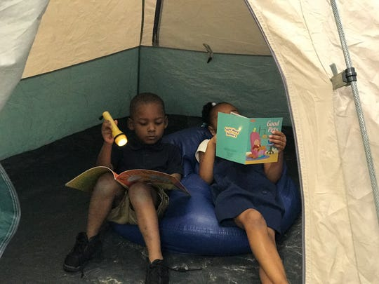 Campers in Lana Rolen's kindergarten group read with flashlights during a camping-themed summer school focused on literacy.