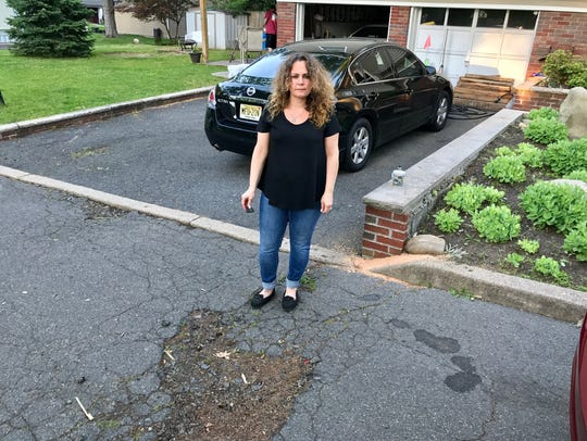Michelle Paolacci stands near a pothole in front of