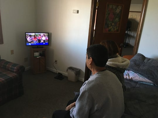 David Chavez-Macias watches TV in a small room. He has been living in sanctuary, afraid of being deported.