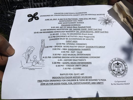 An event volunteer holds a schedule of activities for
