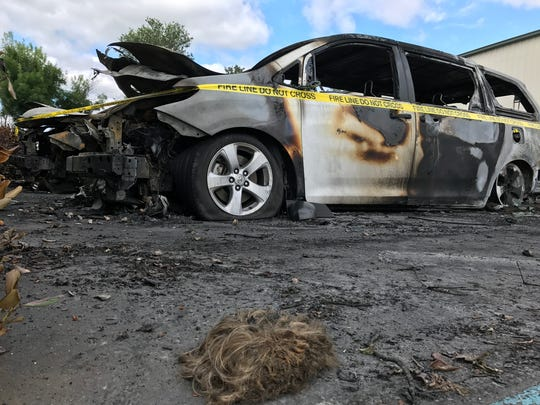 A late Sunday night fire destroyed three minivans and damaged a fourth. The vans belonged to Out and About Shasta County, a nonprofit serving developmentally disabled adults. A half-charred wig is seen nearby.