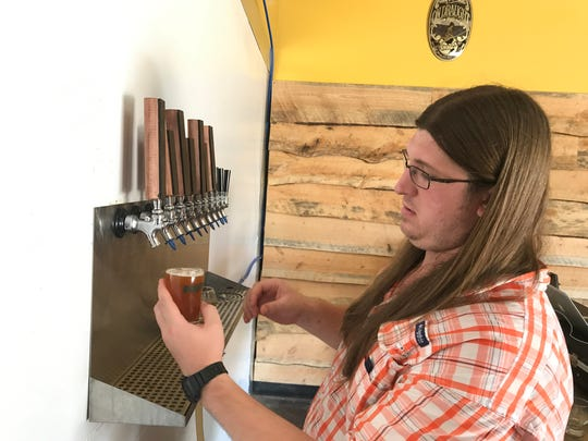 Andrew Brown pours a beer from Golden Grove's 10-tap system. The taphouse is set to open this fall.