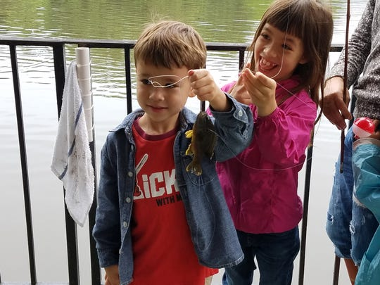 First-time fishers Mito and Io, of Bergenfield, catch a fish at the Bergenfield Fish Derby Saturday, June 17.