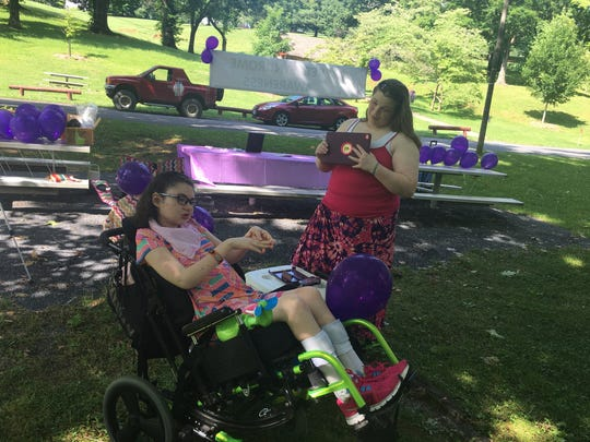 Desiré Zimmerman relaxes at Gypsy Hill Park on Saturday while several of her family members and friends shaved their heads to raise awareness about Rett Syndrome.