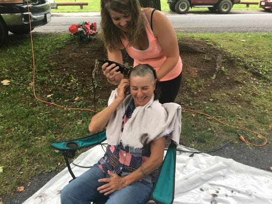 Angela Truelsen smiles as her hair, which hadn't been cut since she was 15 years old, is shaved off Saturday.