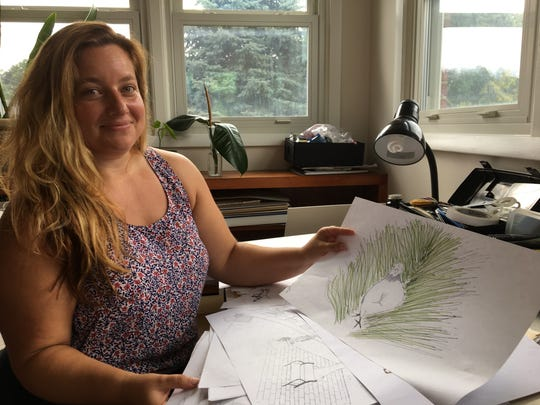 """Director of Beverley Street Studio School and artist Rachel Salatin sits at her drafting table in her home in Staunton with the original illustration of pigeon Patrick that was used for the cover of the children's book, """"Patrick's Great Grass Adventure,"""" she created with her father Joel Salatin, owner of Polyface Farms."""