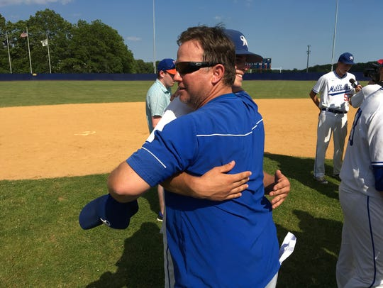 Millburn head baseball coach Brian Chapman (blue) hugs