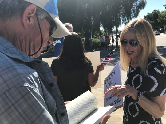 "Tom Seigner of Westlake Village, left, flips through ""The Absolutely True Diary of a Part-Time Indian"" and discusses it with Sue Walsmith of Calabasas."