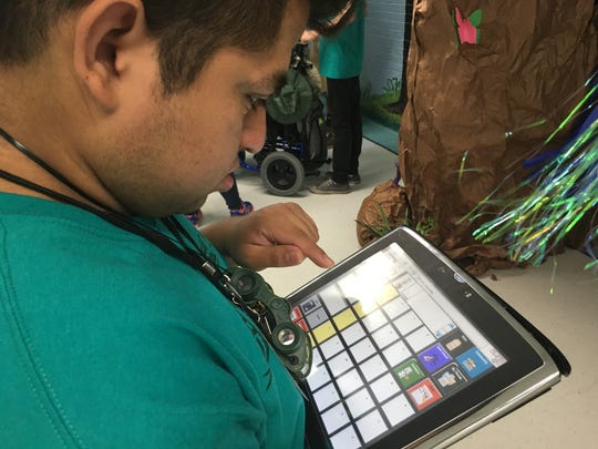 Sebastian Ortiz, 17, uses his digital device to help him speak. Ortiz is in a camp this week that combines learning and fun.