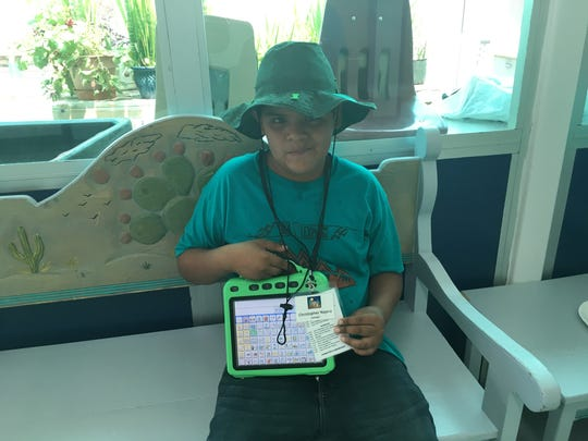 Christopher Najera, 11, shows his digital device, which helps him with his speech. He was learning how to use the device in a summer camp this week.