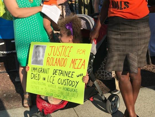 A girl holds a sign to support Rolando Meza Espinoza,