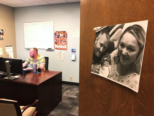 Jeff Fulton works in his office on June 30. A photo of him, his wife and their newborn son is proudly hung on the front of his door.