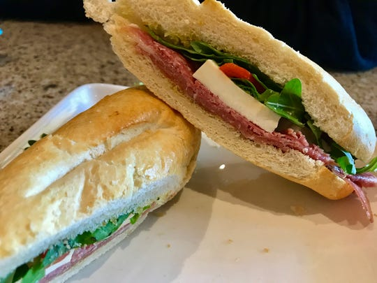 The Paisano is a sandwich with prosciutto, salami, roasted red peppers, arugula and mozzarella.