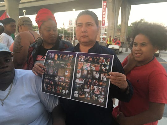Family and friends of Terry Williams hold up a memorial