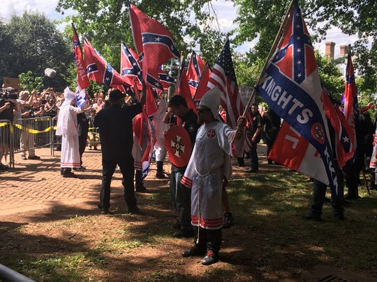 Members of the Ku Klux Klan rally in Charlottesville on Saturday, July 8, 2017, as hundreds more gathered to oppose the even. The KKK is protesting the Charlottesville city council's decision this year to remove a statue of Confederate general Robert E. Lee from a public park and rename that park.