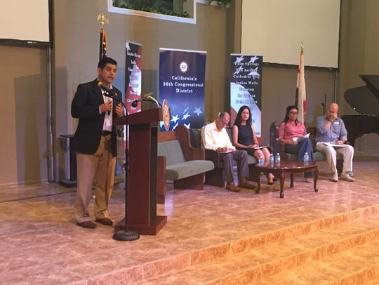 U.S. Raul Ruiz, left, speaks to the audience as panelists