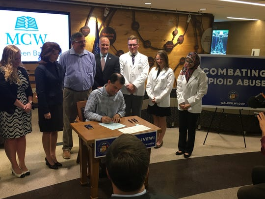 Gov. Scott Walker signs one of four bills that were part of the HOPE agenda to fight opioid addiction at the Medical College of Wisconsin in De Pere.