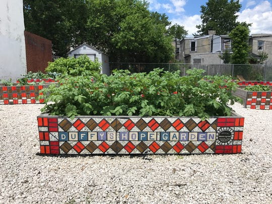 Artists from the Creative Vision Factory installed mosaics on planters at the Duffy's Hope Youth Garden in Eastside.