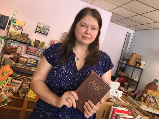Julia Sabin, co-owner of Staunton books, holds up a Russian book — one she read as a child and still reads.