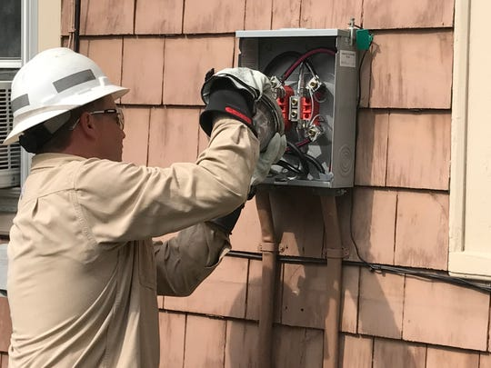 A New York State Electric & Gas Corp. technician installs the company's first smart meter on July 20, 2017 as part of a pilot project in Ithaca.
