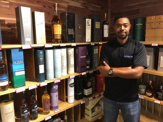 Chris Finch, store manager of Mega-Bev, poses in the