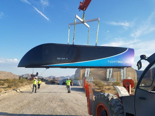A Hyperloop One pod gets craned into position at the