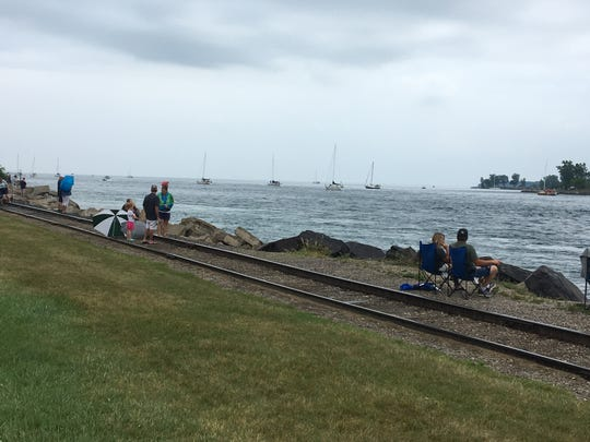 People sit nearby the Blue Water Area Bridge as the 93rd running of the Port Huron-to-Mackinac Island sailboat race begins.