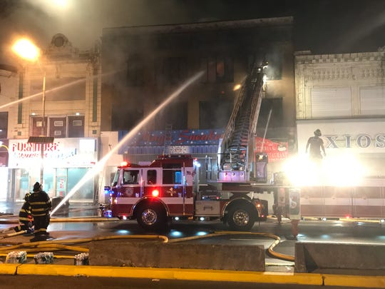 Firefighters battle a four-alarm blaze that sparked in a Main Avenue building in Passaic on Sunday night.