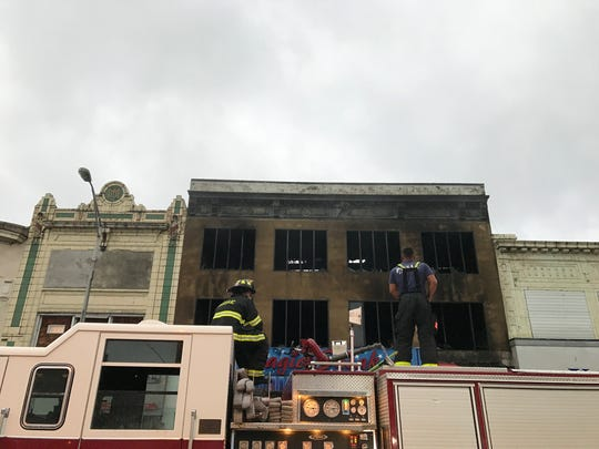 Two members of the Passaic Fire Department monitored the three story building that caught fire Sunday night and raged until the early Monday morning hours.