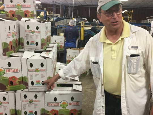 New Jersey's Secretary of Agriculture Doug Fisher points to Jersey Fresh logos on Sun Valley Orchards' bell pepper boxes that will be shipped from Canada to Mexico.