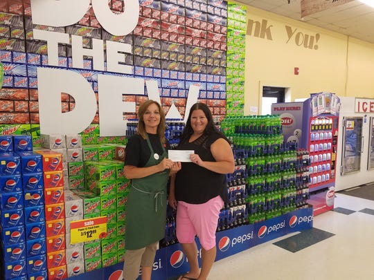Community Market Cashier Korilee Hatmaker, left, presents the store's fund-raising check to Oak Harbor Area Chamber of Commerce Director Valerie Winterfield.