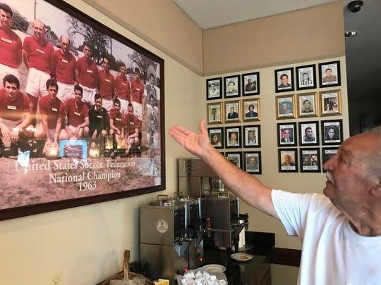 Eddie Castrecchini looks at the 1963 photo of club members, when he was a soccer player.