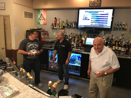 Joe Larizza, front, works the bar at the Sport Club with Nick Pavia, center and Peter LePore