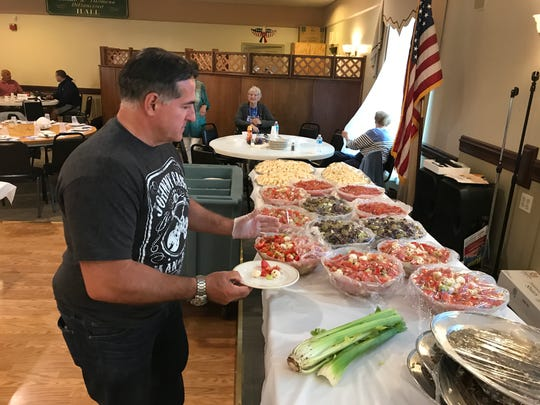 Sport club member Peter Lepore help set the antipasto for luncheon.