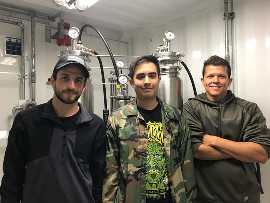 From left, Tyler Tracy, Gabriel Rodriguez and Nieko Jackson in front of the machines that extract cannabis oil