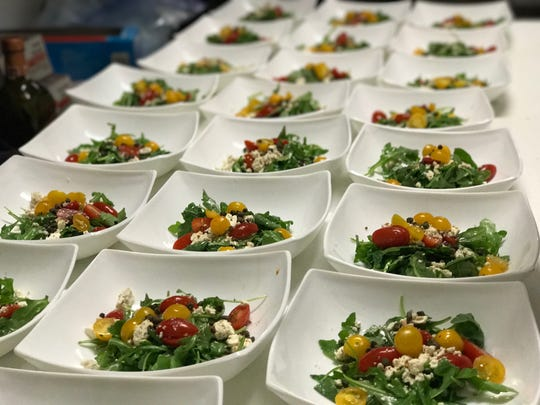 Salads are lined up before being served at one of Vino