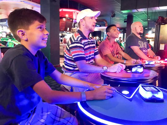 Big Brother Alex Fuller (left center) and his Little Brother Malachi Duran (right center) play a round of Pac Man with fellow Bigs and Littles during an event at Dave and Busters on July 15.