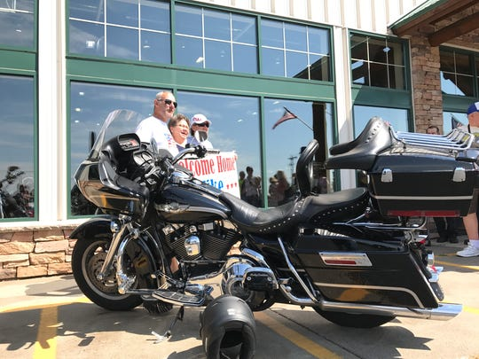 Mike Spaude poses for photos by his bike with his wife Jane Spaude, center, on Friday, July 28, after an 18-day motorcycle ride across the country.