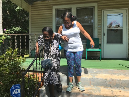 Rosa Vera helps her grandmother Lois Jenkins down the steps of her home on North Leach Street in West Greenville.