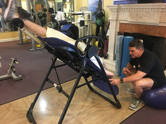 Jon Bates, owner of Addicted to Fitness, works one-on-one with Helen Daniels, 90, on an inverted table. The equipment is helpful for bad backs.