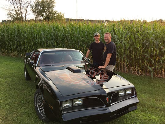 Max Bontekoe, left, and dad Jake Bontekoe show off the 1999 Trans Am they restored together.